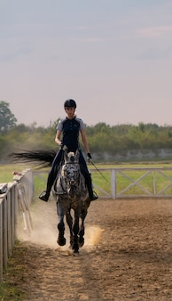 Mooie jonge vrouwelijke jockey op een paard buitenshuis. vrouwelijke atleet rijdt een paard op open manege