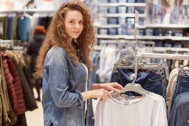 Mooie jonge vrouwelijke klant met krullend haar, draagt spijkerjasje, kiest nieuwe trui