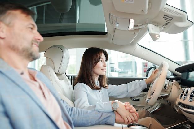 Mooie jonge vrouwelijke klant van hedendaags autocentrum die tijdens een proefrit van een nieuwe auto met haar man op het stuur vasthoudt voordat ze hem koopt
