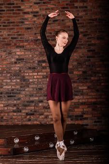 Mooie jonge vrouwelijke klassieke balletdanser op pointeschoenen die een zwarte maillot en rok op een baksteen dragen