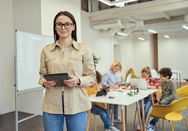 Mooie jonge vrouwelijke leraar met een bril die naar de camera kijkt en tablet-pc vasthoudt terwijl hij in staat