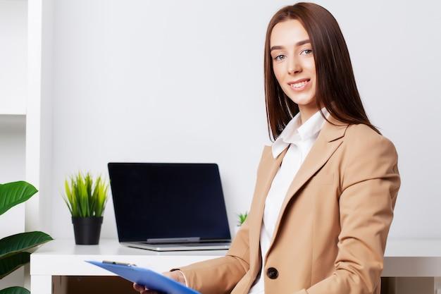 Mooie jonge vrouwelijke manager die met documenten in het bureau werkt