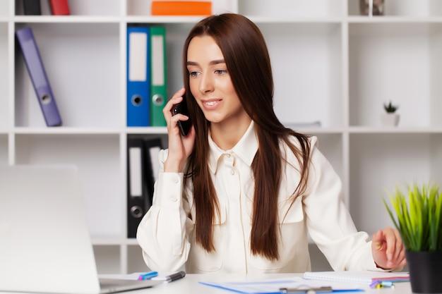 Mooie jonge vrouwelijke manager die op de telefoon spreekt terwijl het werken aan laptop in het bureau