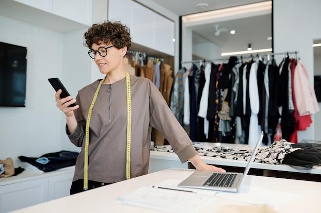 Mooie jonge vrouwelijke modeontwerper scrollen in smartphone of kijken door berichten van klanten