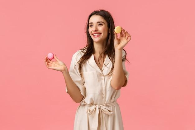 Mooie jonge vrouwelijke ondernemer die een eigen bedrijf begint, desserts bakt, suggereert vrienden te proberen, macarons vast te houden en vrolijk te glimlachen, geamuseerd naar links kijkend, roze muur blij