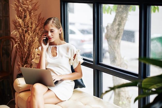 Mooie jonge vrouwelijke ondernemer e-mails op laptop controleren en telefoontjes van klanten beantwoorden
