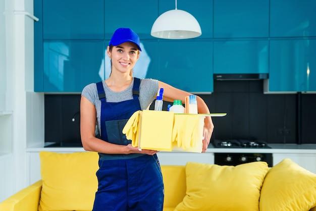Mooie jonge vrouwelijke professionele reiniger in speciaal uniform met hoofdtelefoon wassen van de vloer met dweil en luistert naar muziek in appartement.