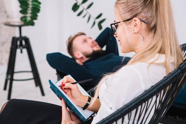 Mooie jonge vrouwelijke psycholoog schrijven van notities in dagboek terwijl patiënt liggend op de bank