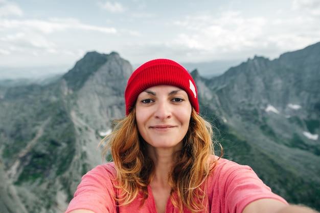 Mooie jonge vrouwelijke toerist maakt selfie in bergen lifestyle avontuur concept actieve vakanties buiten