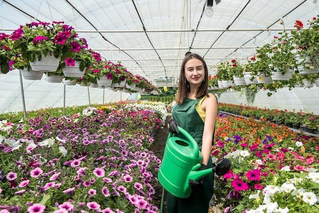 Mooie jonge vrouwelijke tuinman in schort planten in bloemenkas water geven. concept van het verzorgen van planten Premium Foto