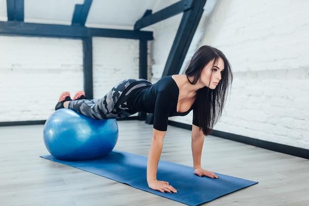 Mooie jonge vrouwelijke uitoefenen met blauwe pilates bal thuis geschiktheidsvrouw het beoefenen van yoga!