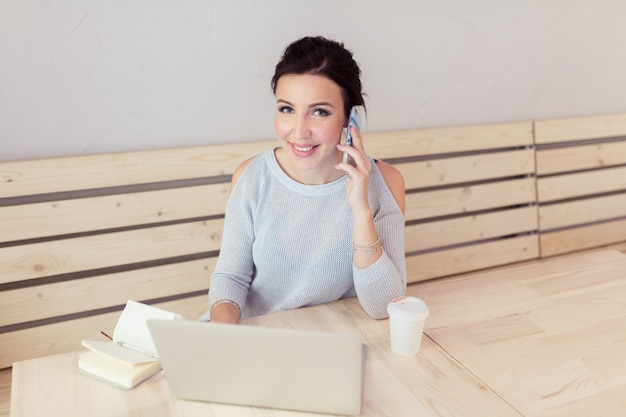 Mooie jonge vrouwelijke volwassene met mobiele telefoon tijdens het werken op laptopcomputer aan bureau naast koffiekopje
