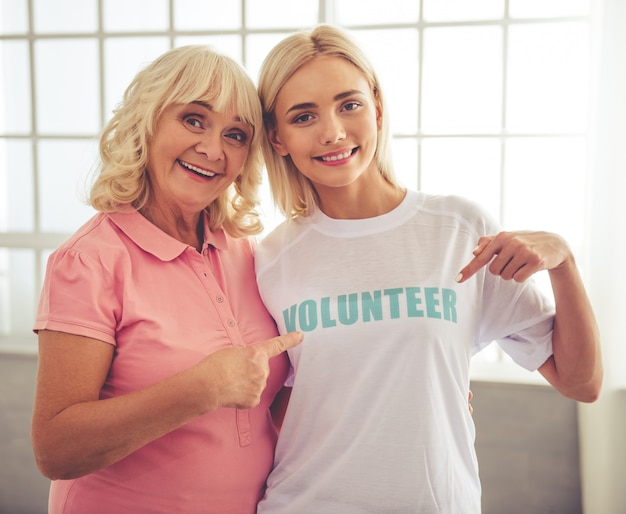 Mooie jonge vrouwelijke vrijwilliger en mooie oude vrouw.