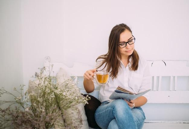 Mooie jonge vrouwelijke vrouw in stijlvolle bril gekleed in modieuze casual kleding zit op een bankje met een notebook en een kopje thee