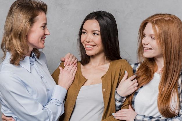 Mooie jonge vrouwen die bij elkaar glimlachen