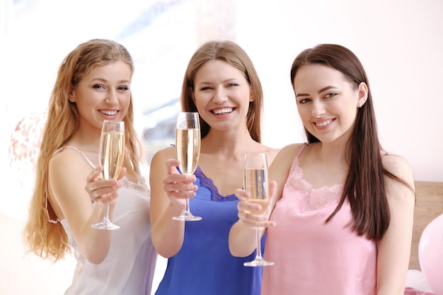 Mooie jonge vrouwen die champagne drinken op vrijgezellenfeest
