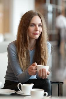 Mooie jonge vrouwen die koffie in een koffie drinken. ondiepe scherptediepte.
