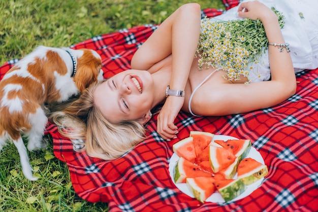 Mooie jonge vrouwen die op de plaid dichtbij watermeloen leggen, die met de hond spelen. natuur, picknick.