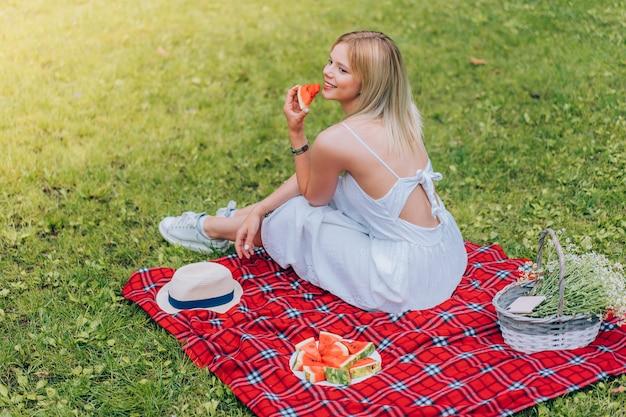 Mooie jonge vrouwen die op de plaid zitten en watermeloen eten. natuur, picknick.