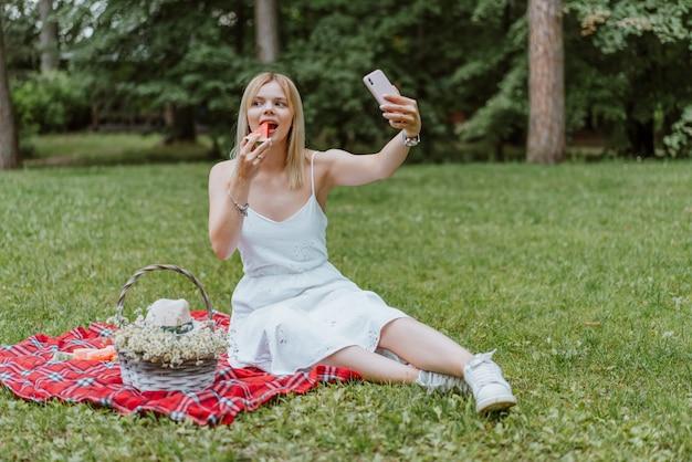 Mooie jonge vrouwen die op de plaid zitten, watermeloen eten, die selfie maken. natuur, picknick.