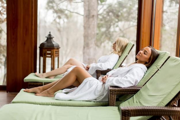 Mooie jonge vrouwen die op de strandstoel bij het zwembad ontspannen