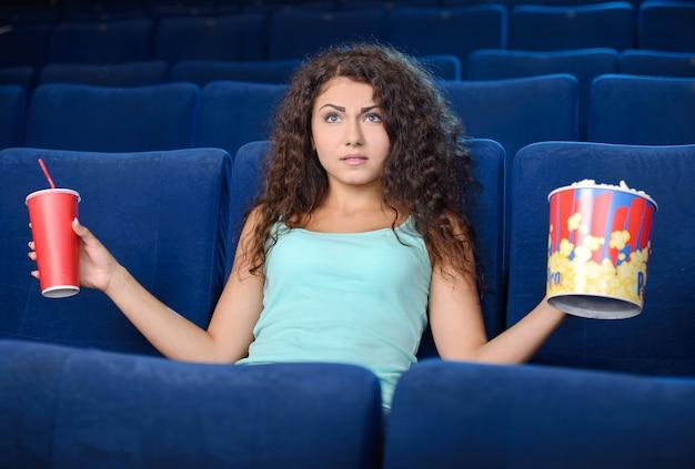 Mooie jonge vrouwen die popcorn eten terwijl het letten van op film