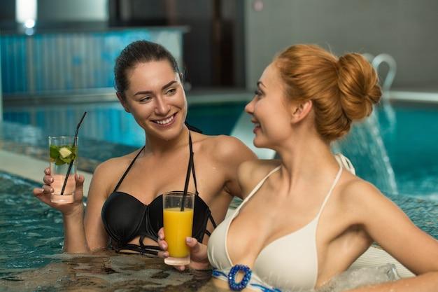Mooie jonge vrouwen die samen in jacuzzi ontspannen