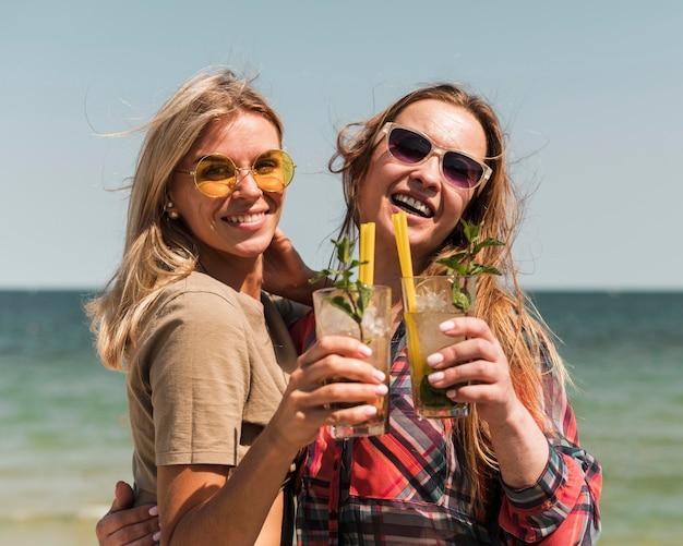 Mooie jonge vrouwen die van zomercocktails genieten