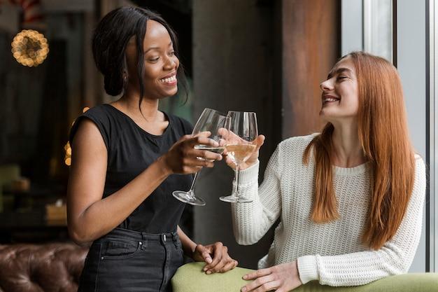 Mooie jonge vrouwen die wijnglazen roosteren