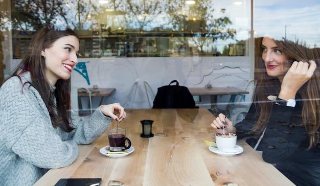 Mooie jonge vrouwen drinken thee in een koffiewinkel.