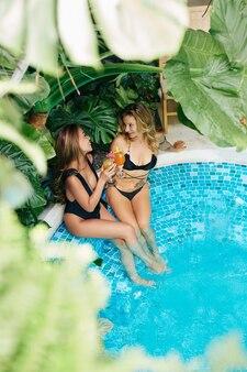 Mooie jonge vrouwen in zwemkleding die in het zwembad staan, kletsen en cocktails drinken