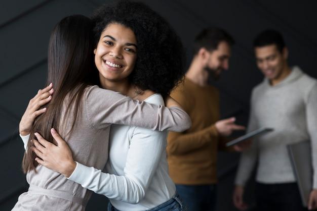 Mooie jonge vrouwen knuffelen elkaar