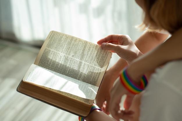 Mooie jonge vrouwen lgbt lesbische zittend op het boek van de banklezing samen