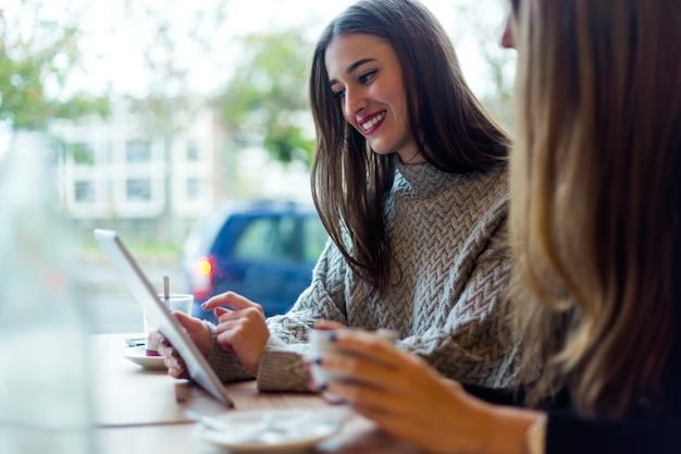 Mooie jonge vrouwen met behulp van digitale tablet in de koffiewinkel.