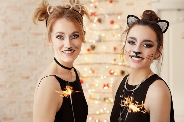 Mooie jonge vrouwen met kattenmake-up en sterretjes op feestje