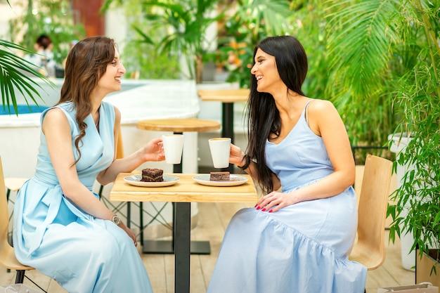 Mooie jonge vrouwen met koffiekopjes op caféterras