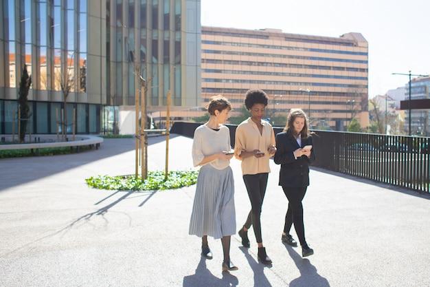 Mooie jonge vrouwen praten tijdens het wandelen op straat