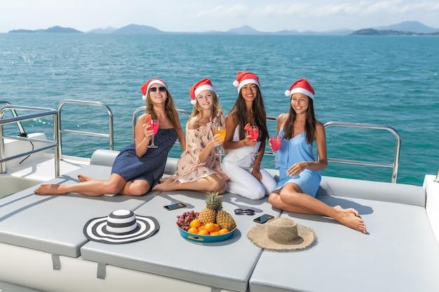 Mooie jonge vrouwen vieren kerstmis in hoeden met drankjes en fruit op jacht
