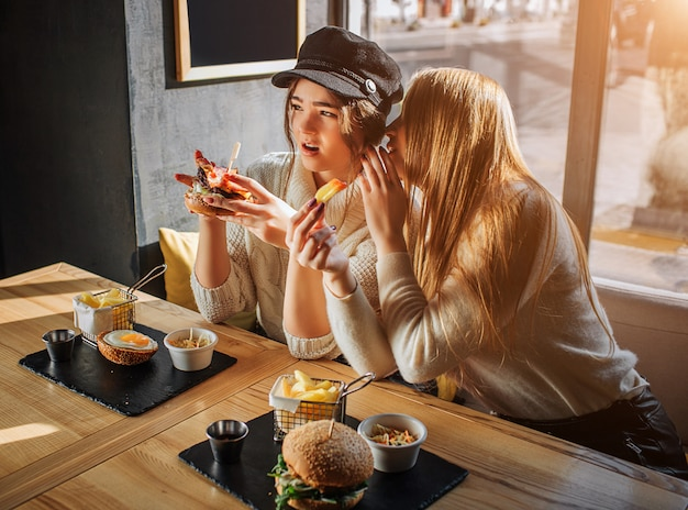 Mooie jonge vrouwen zitten aan de zijkant aan tafel