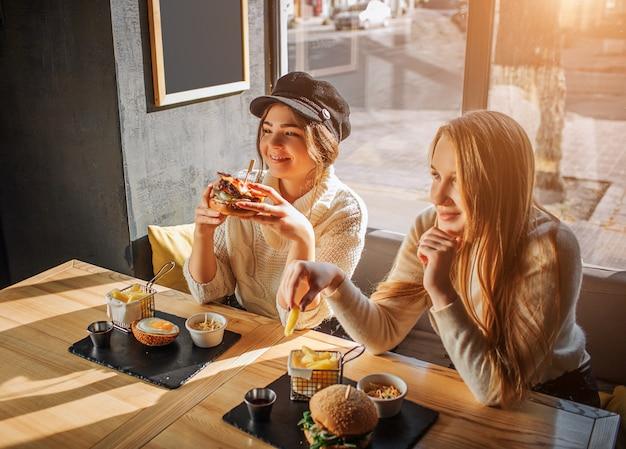 Mooie jonge vrouwen zitten in café aan tafel