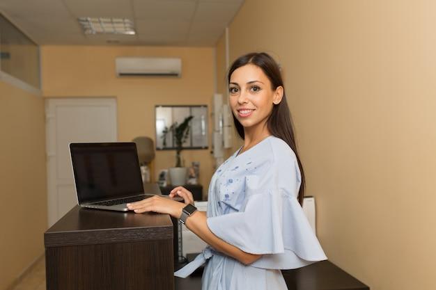 Mooie jonge vrouwenbeheerder bij ontvangst die bij laptop werkt.