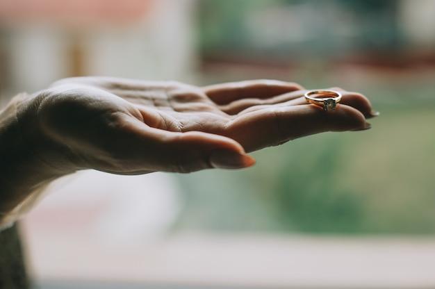 Mooie jonge vrouwenhand die een ring op open palm houdt