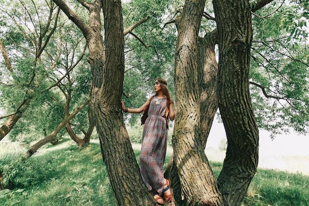 Mooie jonge vrouwenhippie dichtbij een grote boom