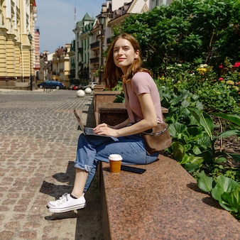 Mooie jonge vrouwentoerist met meeneemkoffie in het stadscentrum die laptop met behulp van.