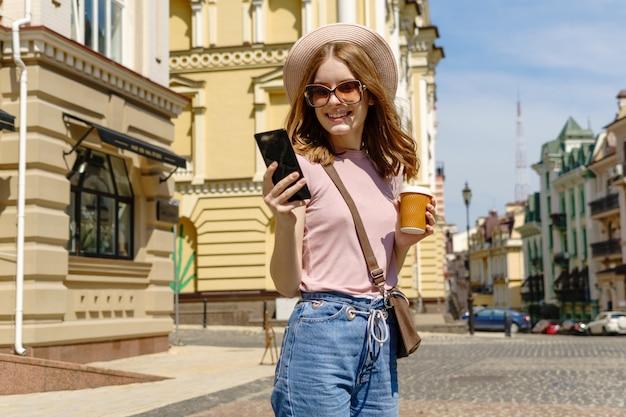 Mooie jonge vrouwentoerist met meeneemkoffie in het stadscentrum die op de telefoon spreken.
