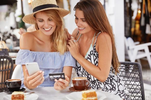 Mooie jonge vrouwentoeristen brengen zomervakanties door in het buitenland, boeken online kaartjes met smartphone en plastic kaart, brengen vrije tijd door, zitten samen in de coffeeshop, drinken espresso of latte.