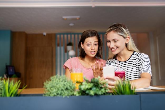 Mooie jonge vrouwenvrienden die mobiele telefoon samen gebruiken en plezier hebben