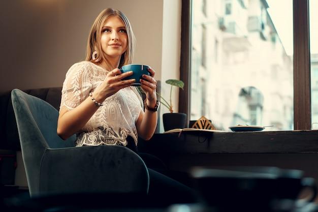 Mooie jonge vrouwenzitting in koffiewinkel die van haar drank geniet
