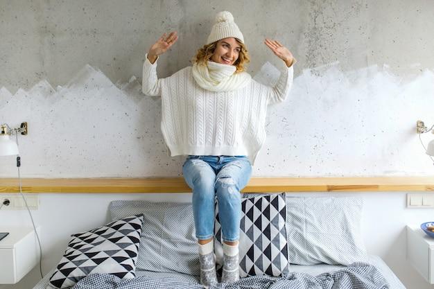 Mooie jonge vrouwenzitting in slaapkamer tegen muur die witte sweater draagt