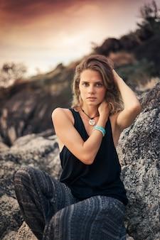 Mooie jonge vrouwenzitting op de rotsen bij zonsondergang